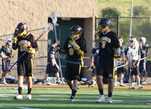 Foothill Knights JV lacrosse defensemen #19 Chance Cooper, #9 Connor Cummins, and #7 Sean Feeney take position at the start of the 3rd quarter against La Costa Canyon Saturday as the La Costa Canyon varsity filed in and watched from the sidelines.
