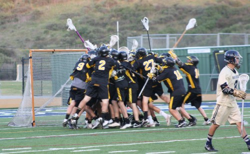 The Foothill Knights JV lacrosse team mobbed goalie Zack Schenker at the end of their 8-4 victory over La Costa Canyon on Saturday, March 28.
