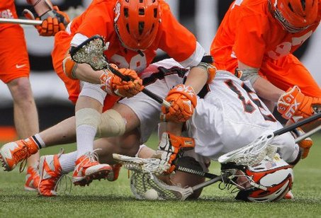Princeton's Paul Barnes (bottom) tries to get his stick on the ball as he goes down with Syracuse's Josh Knight (left) and Tyler Hlawati (right) on top of him in the Big City Classic at Giants Stadium. Princeton won, 12-8.