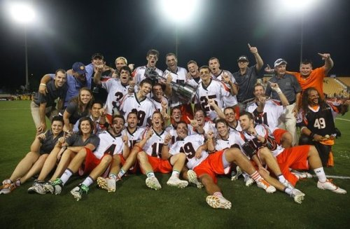 After nine straight years of making it to the post-season, the Denver Outlaws have finally clinched the Championship Title. The Outlaws, who were playing in their fifth MLL championship, are the only team to have made the playoffs in each year of existence. Led by veteran coach BJ O'Hara and unstoppable veteran John Grant Jr., both of whom had previously won a championship with the Rochester Rattlers, the squad was finally able to take the Steinfeld Trophy home to Denver. The Outlaws began the season on a regular season win streak that dated back to the 2012 season. The streak lasted 25 games until Denver fell in a 18-15 decision to the Charlotte Hounds on the road in Week 6. They would continue to flip flop between wins and losses for the rest of the season, suffering big injuries, including losing faceoff specialist Anthony Kelly towards the end of the regular season. However, led by a solid company of veterans, the Outlaws were able to find their rhythm just in the nick of time, beating the Lizards by one goal in the semifinals to lead them to Atlanta.  John Grant Jr. has long been one of the best players in lacrosse, and his skills became even harder to deny after his Coca Cola MVP performance during the Championship match. Junior started out the season slow, but came back with vengeance for the second half, becoming a major impact player for the Outlaws. What's different about this Outlaws team is the range of players on their roster. They had multiple games where over 7 players scored, including the Chesapeake win when nine different Denver athletes found the back of the net. The offense wasn't the only place their players shone through. Their depth is seen on all parts of the field, including in net when back-up goalie Charlie Cipriano won Defensive Player of the Week after stepping in for veteran net-minder, Jesse Schwartzman. It was the roster depth that made the difference at the end of the 2014 season. The Outlaws not only have a solid defensive unit and stellar attackers, but they had one of the deepest midfield rosters in the league.  Led by faceoff specialist Anthony Kelly, Denver sets the tone high for midfield play. Jeremy Sieverts and Drew Snider had especially impressive seasons for the Outlaws, Sieverts becoming the two-point weapon scoring seven in the regular season, more than any MLL team. The midfield was able to quickly move the ball through a variety of players' sticks, making it easy for them to be a threat offensively no matter who made it down the field. After finally passing over the championship title hump, the Outlaws are likely to be equally as successful in 2015. John Grant Jr. has proven he is one of the best and most consistent players of all time, and it will be difficult to slow him down. Denver will also be able to use the younger players on their roster to continue to grow, and will likely see even more impressive performances by their midfielders. 2015 could be another title year for this tenacious and skilled cast of athletes.